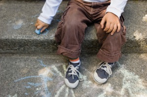 child chalking on step