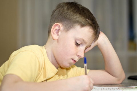 Boy writng head leaning on hand